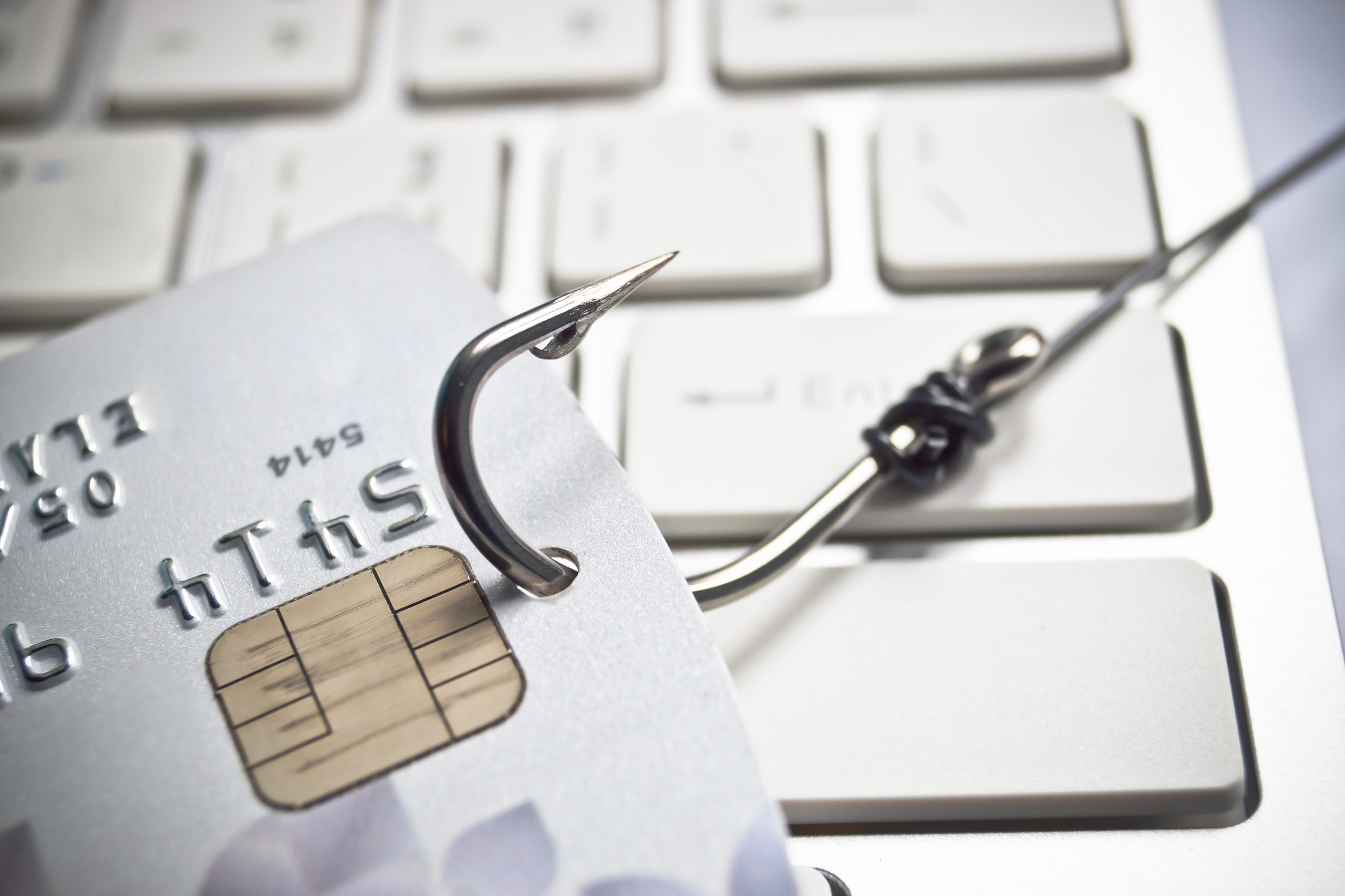 fish hook with a credit card on white computer keyboard